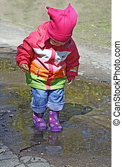 Little Child Standing in Puddle