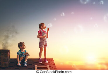 boy and girl playing on the roof - happy childhood! boy and...