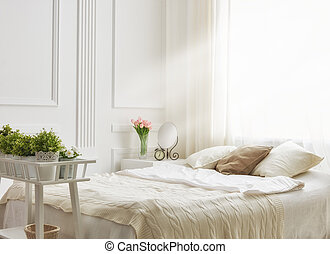 bedroom in soft light colors. big comfortable double bed in...