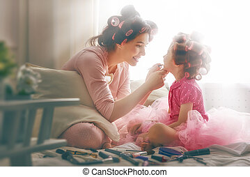 Happy loving family. Mother and daughter are doing hair and...