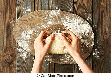 Female hands kneading dough on wooden table