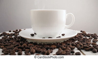White cup with black, hot coffee standing on brown, roasted...