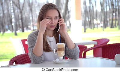 Woman talking on smart phone drinking coffee laughing in...
