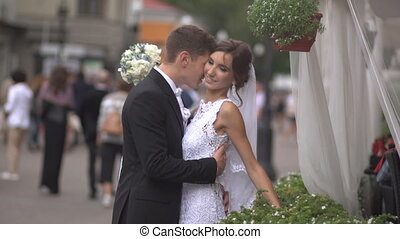 Bride and groom hugging on the street, the bride hesitate -...