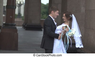 The groom kisses the bride near pillars