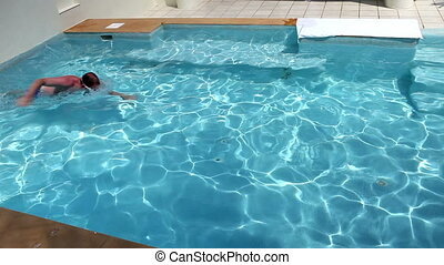 The man swims under water in the pool,