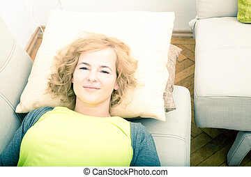 A young smiling woman relaxing on the sofa.