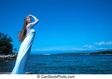 Princess of the night at the ocean - A young beautiful woman...