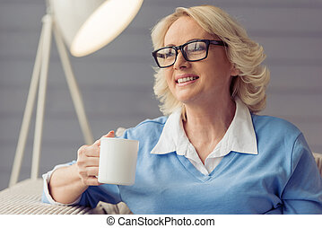 Beautiful old woman in casual clothes and glasses is holding...