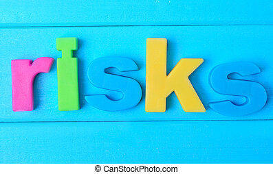 Risks word on table - Risks word on blue wooden table
