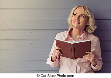Beautiful old woman in classic shirt is holding a book,...
