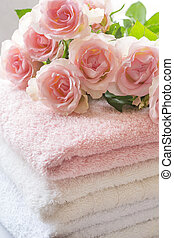Folded towels on bathroom counter with ligh pink roses