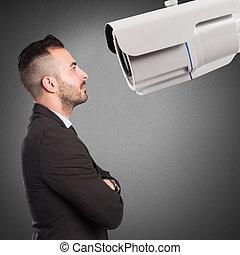Surveillance camera - Man looks at a big surveillance camera