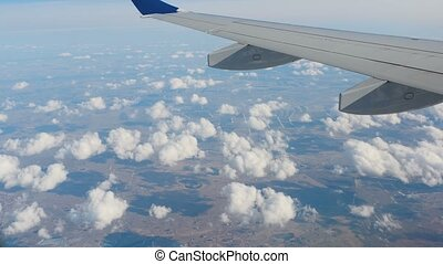 Clouds under the wing of an airplane - Aerial view from the...