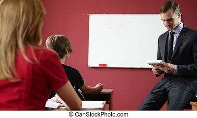 Male teacher giving a lecture at the university students sit...