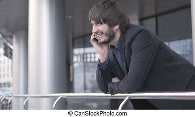 Man with Smart Phone, Young Business Man in Airport. Casual urban Professional Businessman using Smartphone Smiling Handsome man wearing suit jacket outdoors.