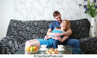 Couple at home relaxing in sofa They embrace and kiss