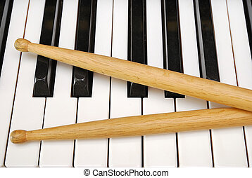 Drum sticks on piano keyboard - Drum sticks on black and...