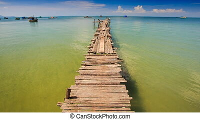 Camera Moves along Long Old Pier Stretching to Boats at...