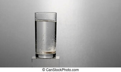 Effervescent Antacid Tablet in Glass of Water. Tablet falls...