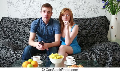 Young couple watching tv on a sofa at home eating potato...