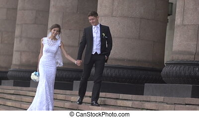 The bride and groom are hand against the background of columns