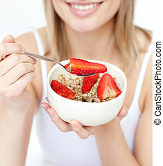 Close-up of a caucasian woman eating cereals with...