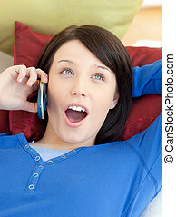 Nice woman laughing on sofa at phone