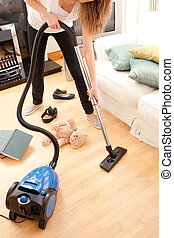 Young woman vacuuming the living-room - Blond young woman...
