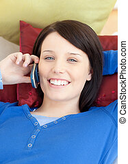 Jolly teen girl talking on phone lying on a sofa in the...