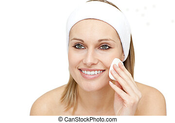 Cheerful woman putting make-up against a white background