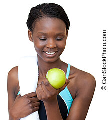 Young fitness woman eating an apple against a white...