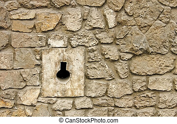 Loophole in medieval masonry stone fortress close-up in...