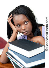 Upset student leaning on a stack of books against a white...