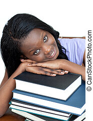 Smiling student leaning on a stack of books