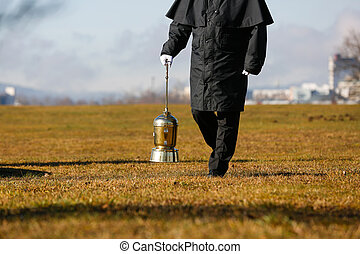 Undertaker carrying an urn with ashes of cremated human -...
