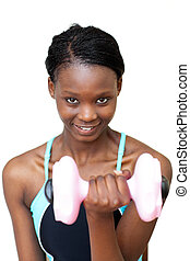 Smiling woman working out with dumbbell against a white...
