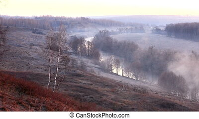 Fog creeps over Osetr river, Russia - Dramatic sunrise with...