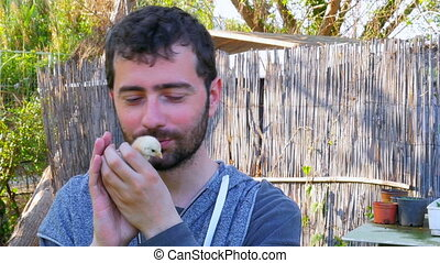 """Caucasian man hold baby chick, kissing holding chicken"""