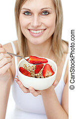 Jolly woman eating cereals with strawberries against a white...
