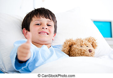 Little boy hugging a teddy bear lying in a hospital bed -...