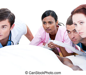 Assertive multi-ethnic medical team resuscitating a patient...