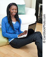 Charming woman using a laptop sitting on the floor