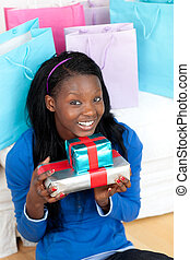 Cheerful woman holding a present sitting on the floor