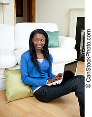 Young woman using a laptop sitting on the floor