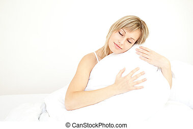 Beautiful woman hugging her pillow sitting on her bed