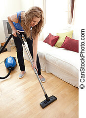 Portrait of a young woman vacuuming at home