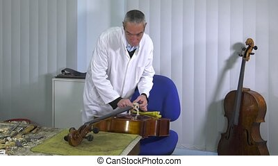 a luthier repairs a cello - luthier positions the strings...