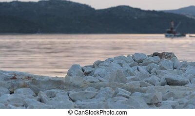 White stones at the sea at sunset