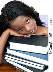 Tired student leaning on a stack of books